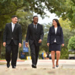 Three business school students walk across campus.