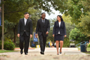 Three business school students walk across campus.