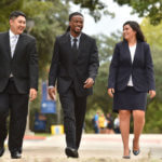 Students in suits walk across campus.