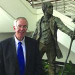 John Haught stands by a bronze statue