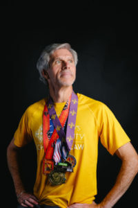 Barry stands with his many medals.