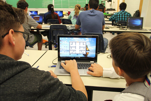 Two middle school students face a computer screen showing a game they have built together