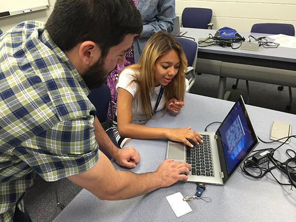 Two students press keys on a laptop keyboard