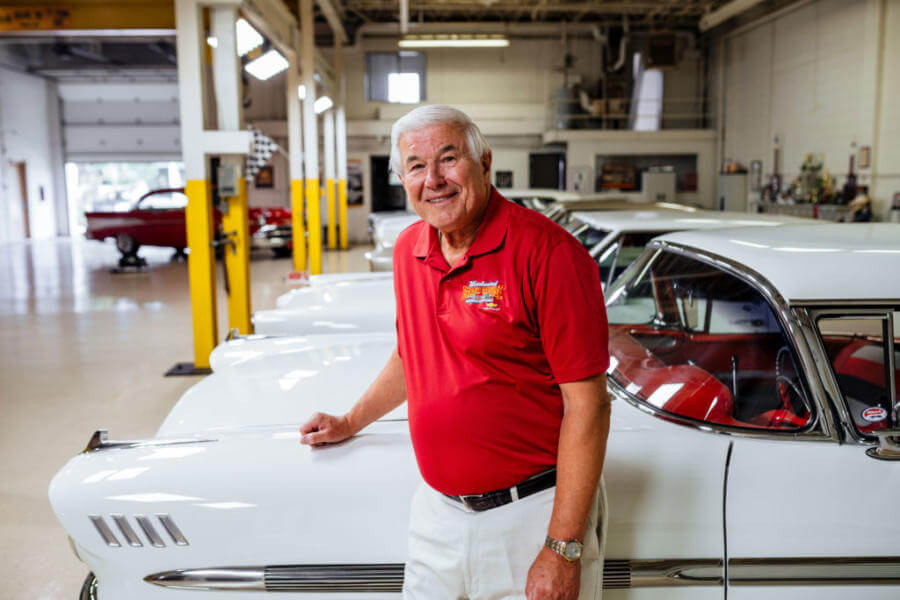Car collector stands in front of his cars in his garage.