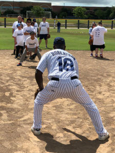 A pitcher in the foreground prepares to throw a ball to campers in the background