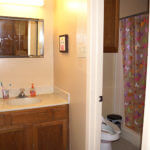 Bathroom in Adele Hall, featuring a room with a shower and toilet, and a separate sink area