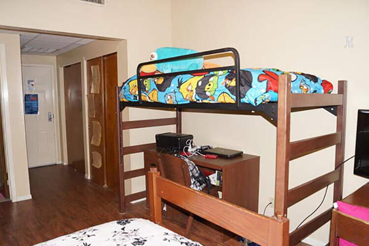 Furnishings of an Adele Hall room: a bunk bed over a desk, separate bed in the foreground