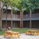 Cremer Hall courtyard, a patio area with two picnic tables surrounded by the brick building