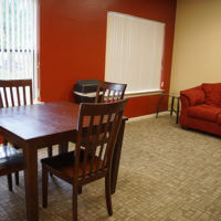 A lounge in Cremer Hall featuring a wooden table with chairs, and a plush couch