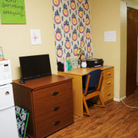 Side view of a bedroom featuring a mini fridge, microwave, dresser and desk