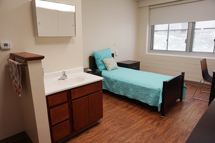 A single bedroom in Chaminade Hall, showing a twin bed and a sink