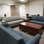 Three couches surrounding a coffee table in a Chaminade Hall lounge