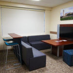 Cozy table and benches surrounding a flat-screen TV inside Chaminade Hall