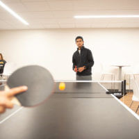 A student's hand and ping-pong paddle blur in the foreground, with focus on the opposing student in the background, playing ping-pong in a lounge in Dougherty Hall