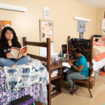 Two female students sit in a Founders Hall room, one on her bed and one reading at a desk