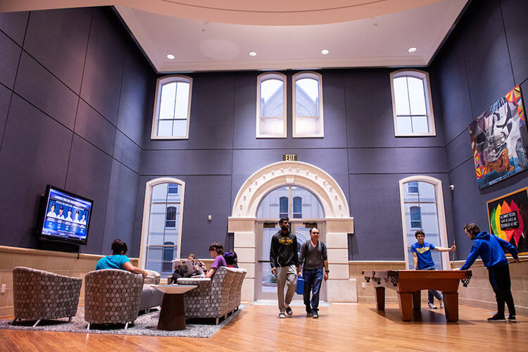 Wide view of a two-story common room in Founders Hall, featuring a seating area and a pool table