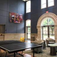 Side view of a Founders Hall common room, featuring a ping-pong table and grand entryway