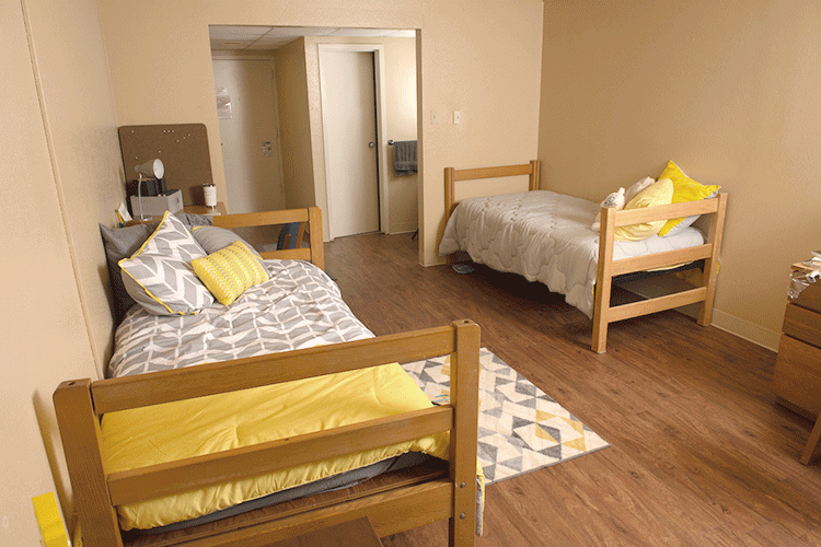 View of a Lourdes bedroom, showing two beds and the entryway in the background
