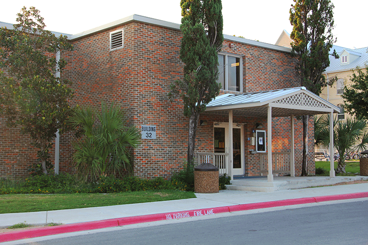 Front entrance of Lourdes Hall, a two-story brick building with a covered entryway