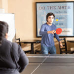Two students play ping-pong in a common room