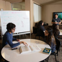 Students study around a common room table in Marian Hall