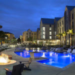Fire pit and patio surrounding the pool at Perigueux at nighttime