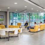 Students sit on couches surrounding a television in a Perigueux lounge