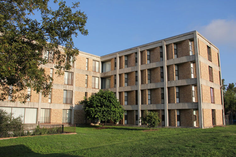 Side view of Treadaway Hall, a four-story brick building