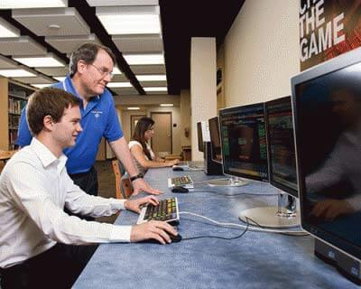 Richard Bauer with a student using a computer