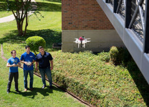 Senior engineering students outside the UC with a drone