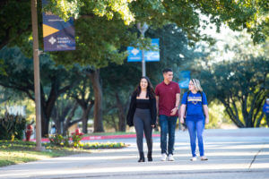 Three students chat as they walk across campus.