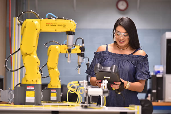 A female engineering student uses a robotic arm to work in a lab.