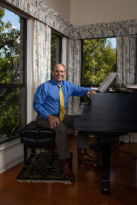 Law alum, Claude Ducloux sitting at piano in his Austin home.