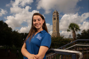 Laura Dicun stands with the Bell Tower behind her.
