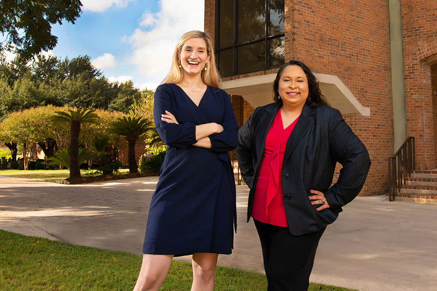 Marina Lewis and Katherine Cabello-Flores stand behind the Raba Building.