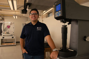 Nicolas Romero stands by Mechanical Engineering equipment.