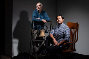 Gerald E. Poyo, left, stands next to the bell from St. Mary's Institute — cast in 1866 — as Edgar Velázquez Reynald sits on the chair of the late Brother Thomas J. Treadaway, S.M. (1897-1869), Registrar for most of his 31 years at St. Mary's.