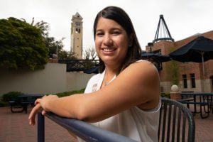 Vanessa Cypert sits with the Bell Tower behind her.