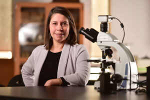 Veronica Contreras-Shannon stands by a microscope.