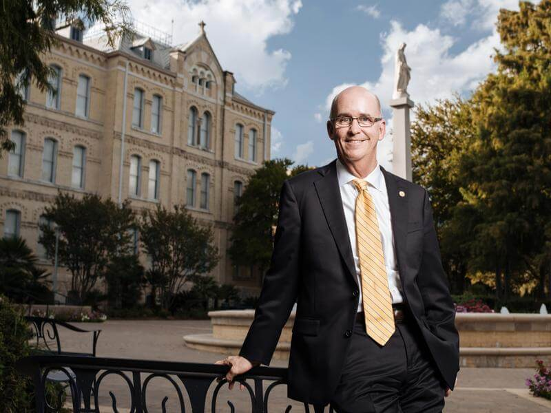 President Tom Mengler stands smiling in front of St. Louis Hall