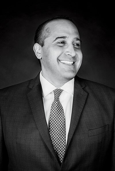 AmirSamandi smiles in a dark suit.