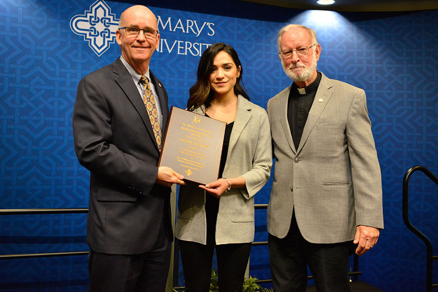 Leslie Alvarez accepts award from President Mengler and Father Eden