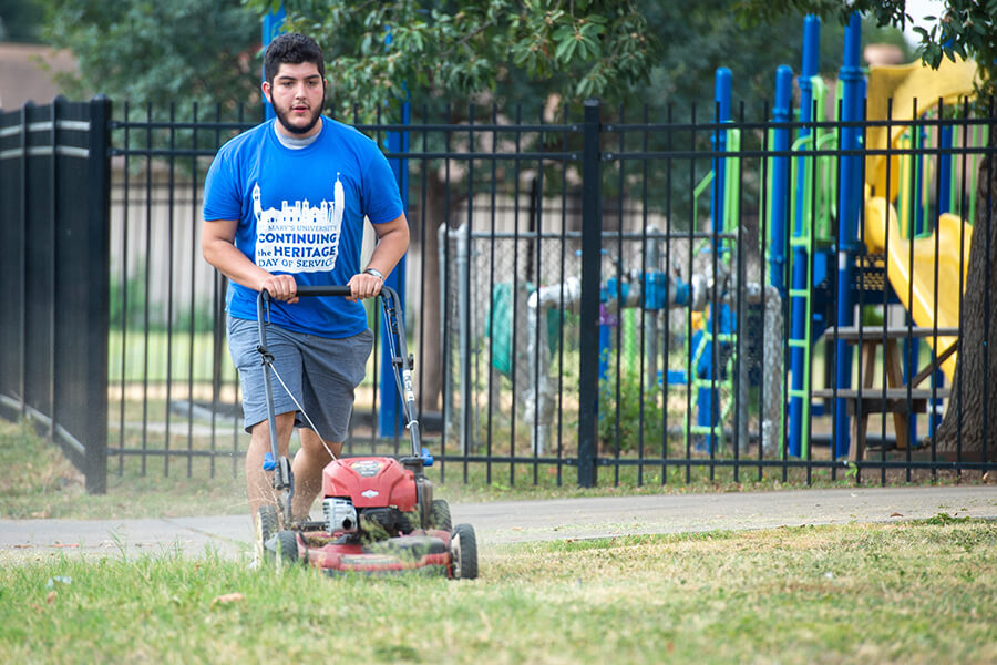 A student helps with yard work during Fall 2019 Continuing the Heritage.