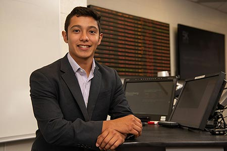 Rudy Martinez stands in the School of Business.