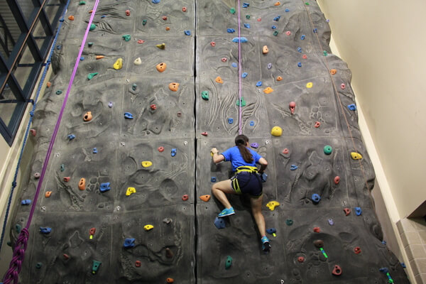 Student climbing the rock wall in the Fitness Center