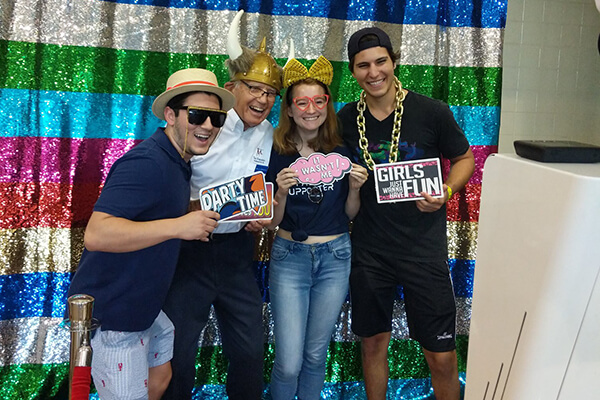 Students pose with a Marianist brother at a photo booth