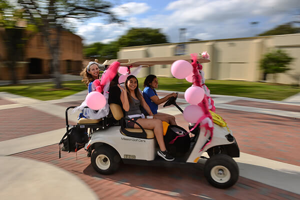 Students participate in the golf cart parade during Homecoming