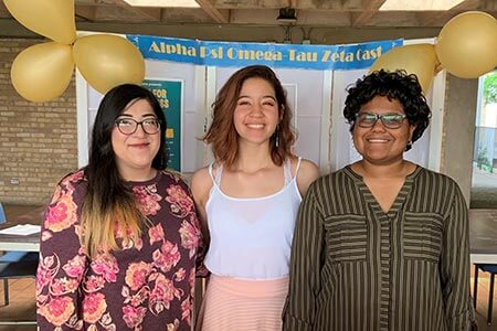 Three female students smiling at a booth promoting Alpha Psi Omega