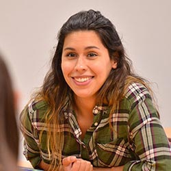 female student in plaid shirt smiling at classmate