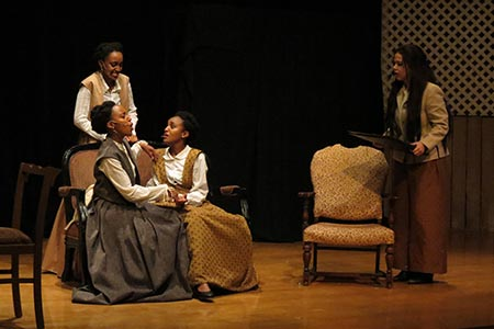 Four female actresses on stage during a production of Little Women